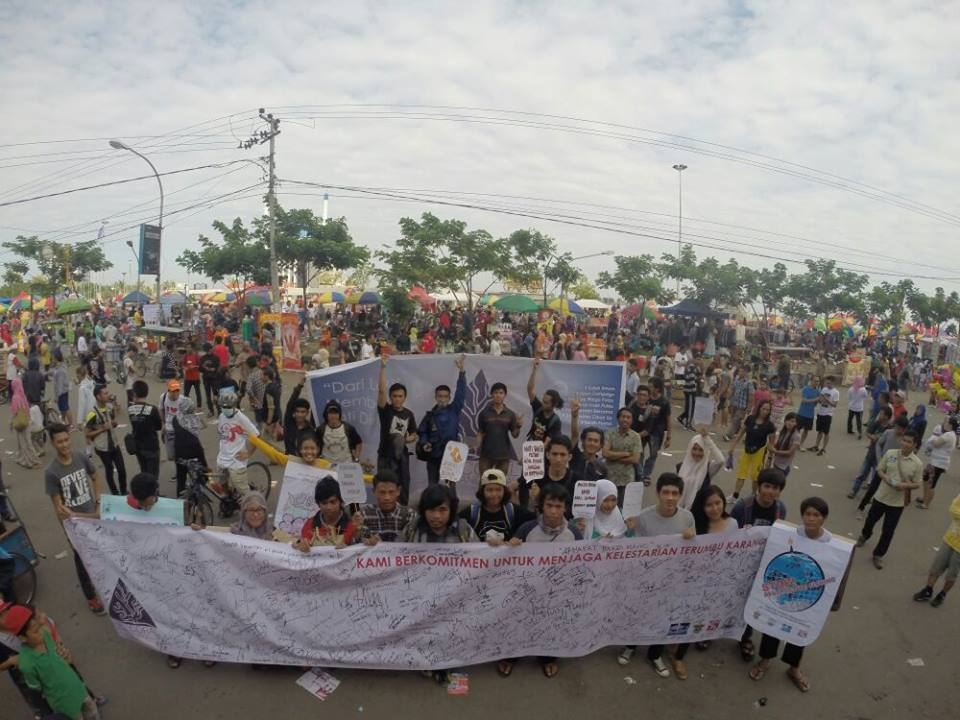 The people of Makassar hold banners of support they signed campaigning on coral reef conservation. — at Losari Beach, Makassar, Indonesia.