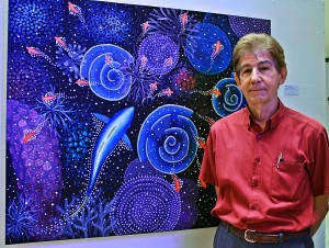 The author, marine biologist and artist, standing beside one of his paintings. (Photo by CTKN)