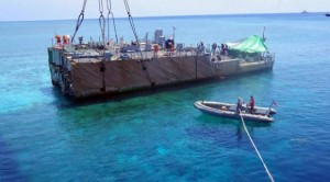 This undated handout photo released on 30 March 2013 by the Philippine Coast Guard (PCG) shows the stern of the USS Guardian before being lifted by a boat crane during its salvage operation at Tubbataha reef, in Palawan island, western Philippines. (Photo courtesy of AFP PHOTO/PCG)