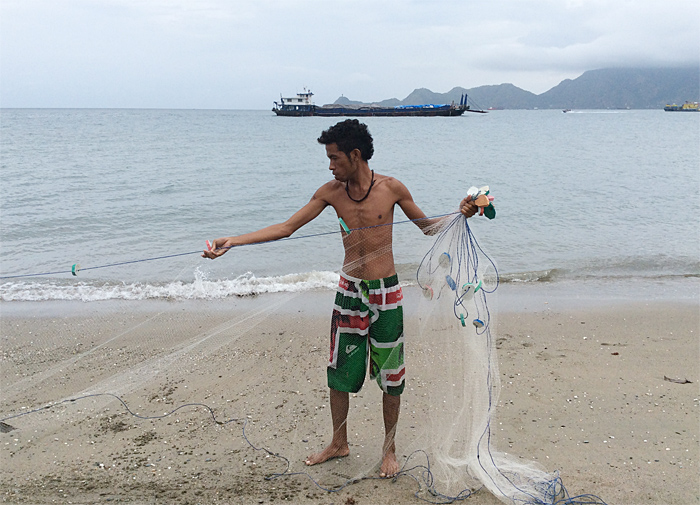 Fisher with his net in Dili, Timor Leste. (Photo by: Marilou Drilon)