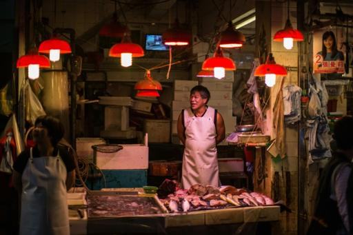 A fishmonger waits for customers in the Wanchai district of Hong Kong on November 3, 2015. (Photo by: Anthony Wallace/AFP News)